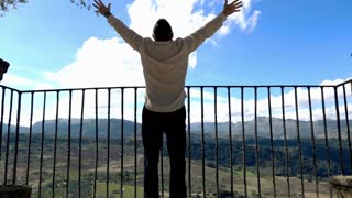 Happy young man enjoying beautiful view from  the view point terrace, super slow motion