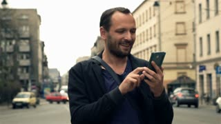 Happy, young man using smartphone in city, super slow motion 240fps