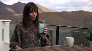 Happy young woman listening to music, singing and dancing on terrace with mountain view, 4K