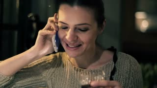 Happy young woman talking on cellphone and drinking wine in bar