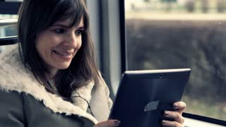 Happy, young woman watching movie on tablet during tram ride