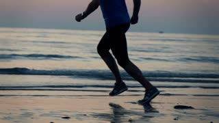 Jogger legs running on the beach during sunse, super slow motion, shot at 240fps