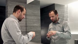 Man applying beauty cream on his face in the bathroom