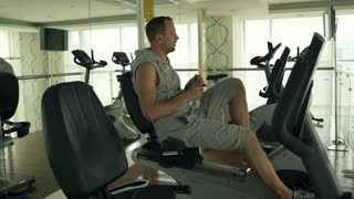 Man drinking water while riding stationary bike in the gym, shot at 240 fps