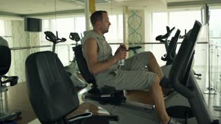 Man drinking water while riding stationary bike in the gym