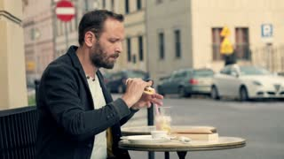 Man eating sandwich and drinking juice while sitting in  outdoor bar