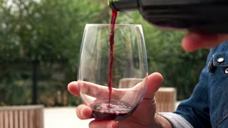 Man hands pouring wine while sitting on the terrace, 240fps