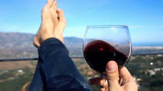 Man holding glass of wine lying on terrace, super slow motion 240fps