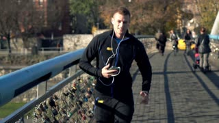 Man jogging across the bridge and listening to the music, super slow motion, 120fps