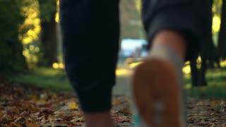 Man jogging in autumn park, super slow motion, focus on legs