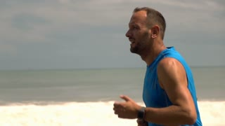 Man jogging on beautiful beach, super slow motion