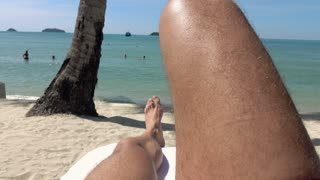 Man legs on sunbed, view on the beach and sea, 4 K