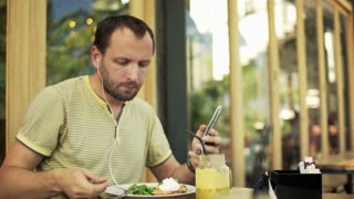 Man listening to music on smartphone and eat salad in cafe in the city
