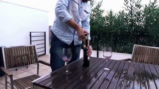 Man opening wine bottle on terrace, super slow motion 240fps