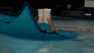 Man reading book lying on mattress by swimming pool, super slow motion