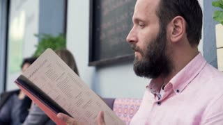 Man reading food menu in cafe
