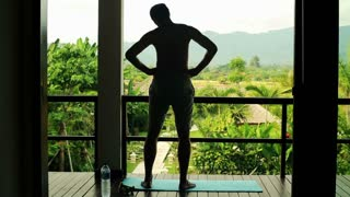 Man doing warm up exercise on luxury terrace with exotic view