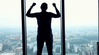 Silhouette of successful man raising arms, power symbol in the office, super slow motion