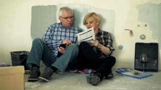 Mature couple counting bills with smartphone sitting on floor at their new home