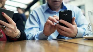 Mature couple hands using smartphone sitting in cafe