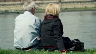 Mature couple hugging close to the river in the city