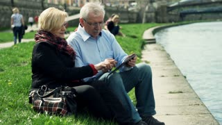 Mature couple sitting with tablet close to the river in the city