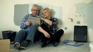Mature couple talking and checking tile sitting on floor at their new home