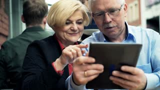 Mature couple talking and using tablet computer sitting in cafe in the city