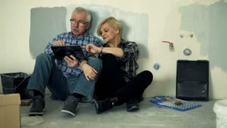 Mature couple talking and using tablet computer sitting on floor at their new home
