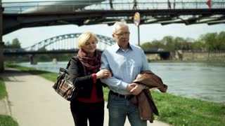 Mature couple talking during walk in city