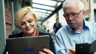 Mature couple using smartphone and tablet computer sitting in cafe in the city