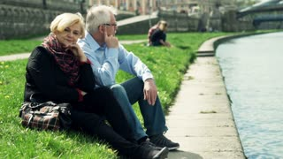Mature, pensive couple sitting close to the river in the city