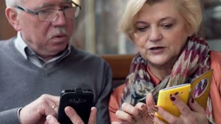 Middle aged couple showing each other something on smartphone in cafe