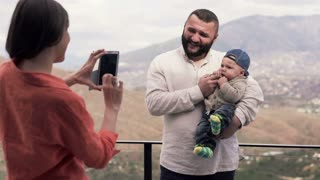 Mother taking photo with cellphone of her husband with small son standing on terrace with splendid view