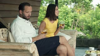 Offended, bored couple sitting onj wooden sofa on terrace
