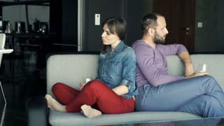 Offended couple sitting on sofa at home