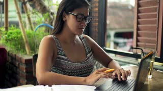 Overwhelmed, sad woman with documents and laptop sitting by table at cafe