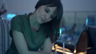 Pensive woman drinking cocktail sitting at rooftop bar during night