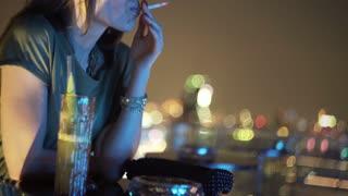 Pensive woman smoking cigarette at rooftop bar during night