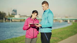 Personal trainer explains exercise to young woman using a tablet in the city river