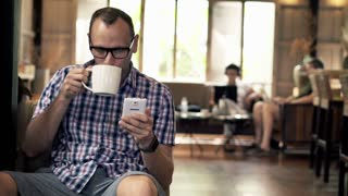 Portrait of handsome man with smartphone and coffee in cafe