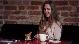 Portrait of happy beautiful woman drinking coffee in cafe