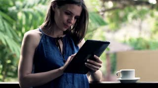 Portrait of happy, beautiful woman with tablet compute standing on balcony