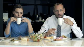 Portrait of happy business couple drinking coffee during breakfast