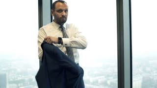 Portrait of happy businessman dressing up suit jacket in the office