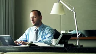 Portrait of happy businessman with laptop sitting by desk at office