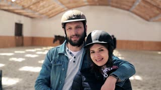 Portrait of happy couple with helmet on the riding lesson at the stable
