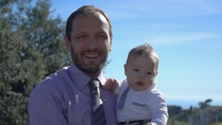 Portrait of happy father with child standing in the park, super slow motion