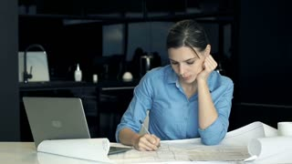 Portrait of happy female architect doing notes on blueprints in the kitchen