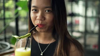 Portrait of happy woman drinking juice in cafe